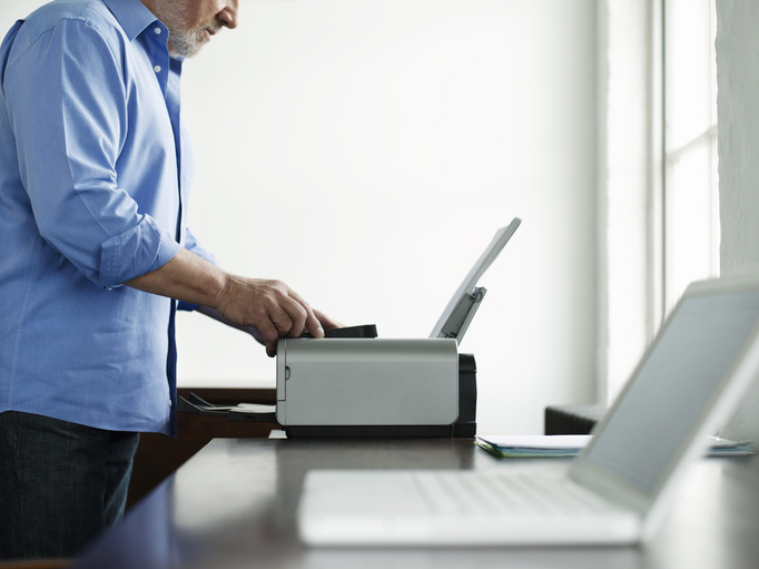 A man working on a home office printer