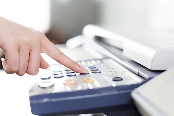 A worker start to scan documents to email by pushing a button on the copier