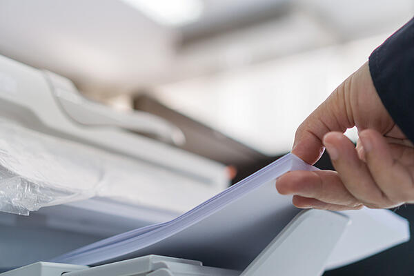 An employee uses one of many types of paper for printing.